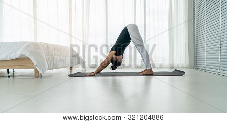 Middle Aged Women Doing Yoga Downward Facing Dog Pose To Meditation With Yoga In Bedroom At The Morn
