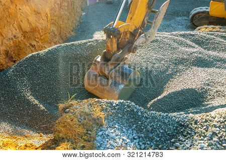 Excavators Moving Gravel In The Construction Works Of A Foundation In The House.