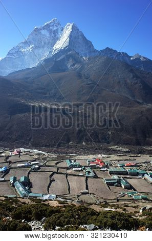 Sagarmatha national park, Dingboche, Nepal - May 20, 2019: View of Dingboche village (4410 m) and Ama Dablam mountain (6856 m) from the trail of Everest trek