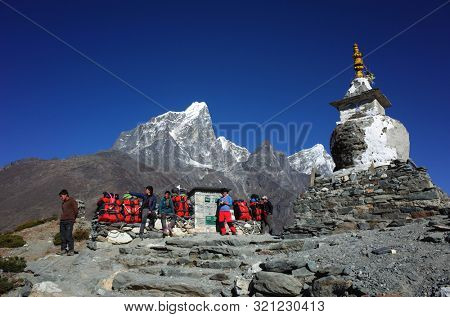 Sagarmatha national park, Dingboche, Nepal - May 20, 2019: Group of porters with red duffle bags resting near old buddhist stupa with view of Tabuche peak (6367 m) on the Everest trek