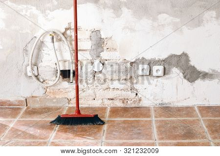 Unfinished Room Reconstruction. Home Repair, Improvement. Work In Progress. Red Broom Against White