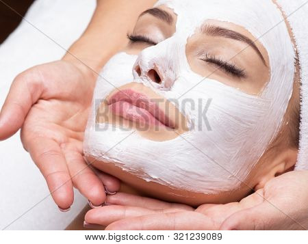 Spa massage for young woman with facial mask on face