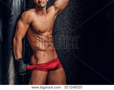 Sexy Handsome Man With Beautiful Muscular Body And Mini Red Pants Is Posing On The Dark Background N