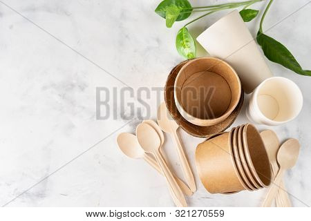 Eco Tableware On Light Green Background. Paper And Bamboo Cups, Bag And Wooden Cutlery