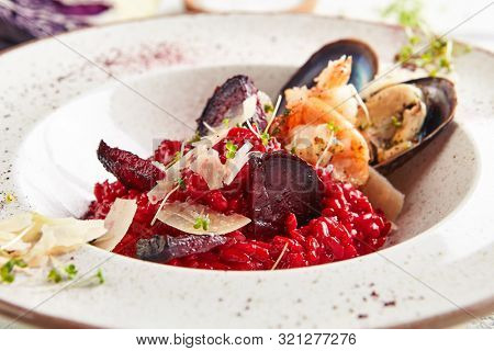Macro shot of red beetroot risotto with chrimps, prowns, mussels and parmesan cheese. Exquisite serving beet seafood paella with shells, greens and spices closeup