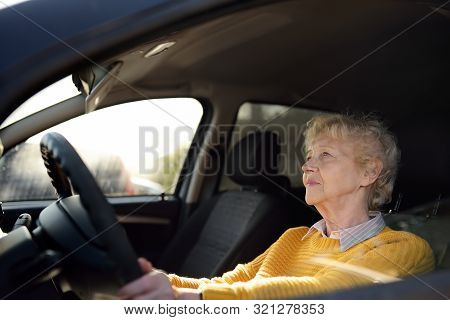 Portrait Of A Senior Business Woman Learning Drive A Car. Unsafety Drive. View Through Side Window.