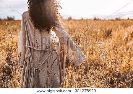 Beautiful Young Woman Walking On A Field At Sunset