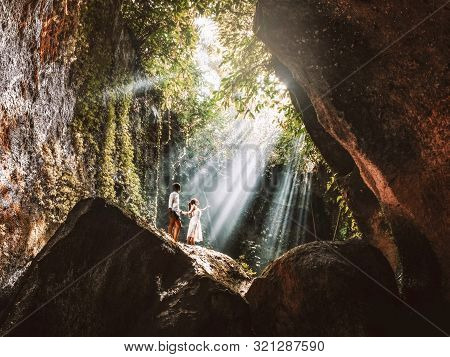 Traveling Young Couple With Tropical Rainforest Rock In Bali Enjoying Life At Beautiful Lighting Hid