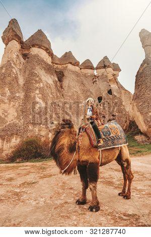 Traveler Woman Riding Camel At Goreme Fairy Chimneys , Cappadocia. Nevsehir Province. Turkey.