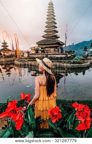 Asian Woman Traveling At Pura Ulun Danu Beratan The Floating Temple In Bali , Indonesia In Morning.