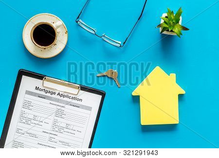House Mortgage With Application, Glasses, Coffee, House Toy, Keys On Blue Banker Desk Background Top
