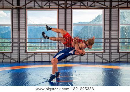 Greco-Roman wrestling training, grappling. Two greco-roman  wrestlers in red and blue uniform wrestling  on a wrestling carpet in the gym.Training and practicing sports throws poster