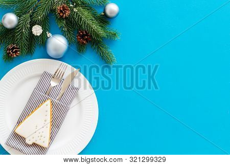 Table Setting With Spruce, Plate, Flatware On Blue Background Top View Mockup