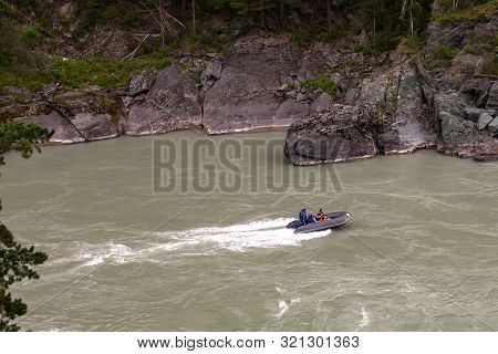 Aerial View Of A Gray Rubber Motor Boat Sailing On A Green River In The Mountains Between Rocks And