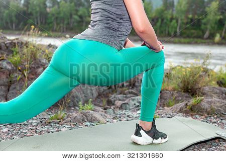Close Up On A Sexy Tight Booty Of Pretty Woman While She Is Doing Stretching By Leaning Against The