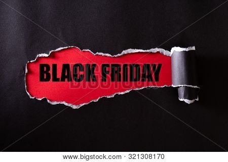 Top View Of Black Torn Paper And The Text Black Friday On A Red Background. Black Friday Composition