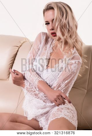 Gentle and seductive blonde woman with attractive body in white lacy lingerie is sitting on sofa. sensual model posing in lace peignoir poster