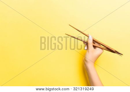 Wooden Chopsticks In Female Hand On Yellow Background With Empty Space For Your Idea. Tasty Food Con