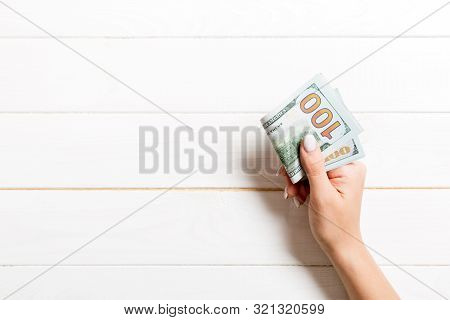 Top View Of Female Hand Holding A Pack Of Money On Wooden Background. One Hundred Dollars. Business