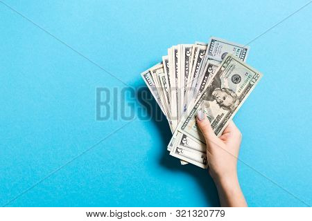 Top View Of Female Hand Giving Various Dollar Bills On Colorful Background. Charity And Donation Con
