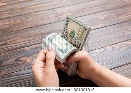 Perspective View Of Female Hands Counting Money. One Hundred Dollar Banknotes On Wooden Background.