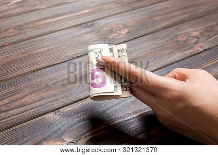 A Pack Of 5 Dollar Bills In Female Hand On Wooden Background. Salary Concept With Copy Space