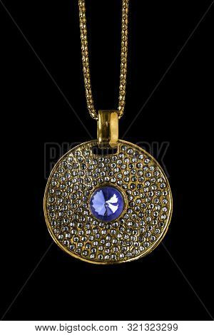 Vintage Gold Pendant With Crystals And One Sapphire Hanging On A Chain On Black Background