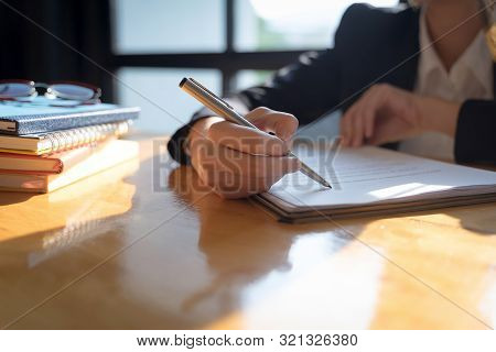 Businesswoman Point To A Contract Paper With Their Pen And Advise Customers To Sign Their Names. Poi