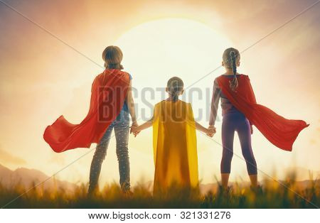 Little children are playing superhero. Kids on the background of sunset sky. Girl power concept