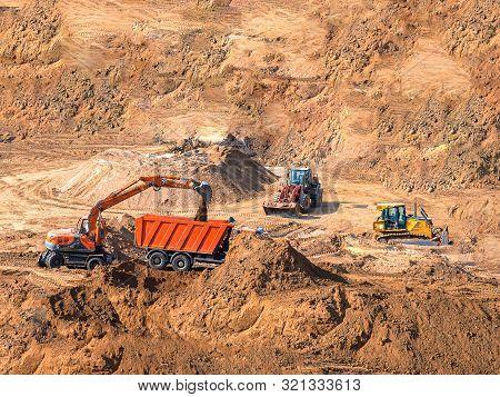 Excavator Loader Machine Loading Dumper Truck At Construction Site. Digger And Wheel Loader Heavy Du
