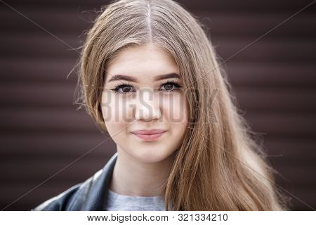 Close-up Portrait Of Little Beautiful Stylish Kid Girl Against A Brown Striped Wall