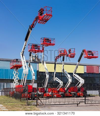 Different Self Propelled Articulated Boom Lifts And One Scissor Lift Red With White Colors On A Back