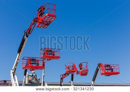 Red Baskets On The White Booms Of Different Articulated Boom Lifts And Top Parts Of Lifts On A Backg