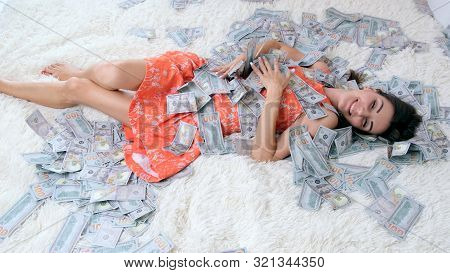 Many Banknotes Fly In The Air Overhead In Slow Motion. A Girl Lies And A Lot Of Money Falls On Her.