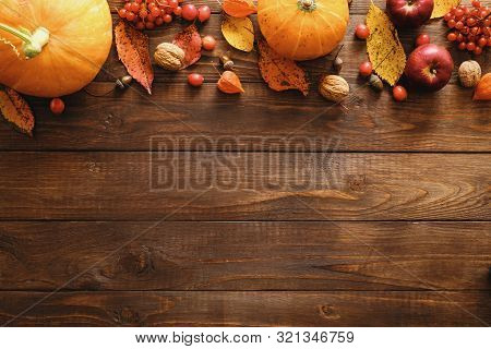 Autumn Frame Border Made Of Pumpkins, Dried Fall Leaves, Apples, Red Berries, Walnuts On Wooden Back