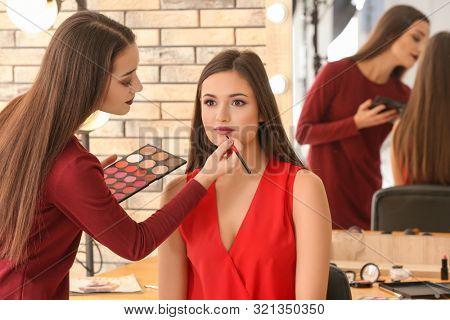 Professional makeup artist working with client in salon