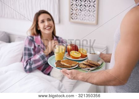 Young handsome man bringing breakfast for his beloved girlfriend in bed