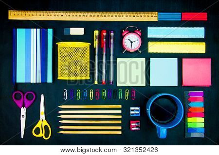 Colorful Office Supplies Neatly Geometrically Evenly Laid Out On Blackboard Background. Pencils, Sci
