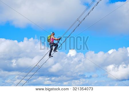 Stairway To Heaven Concept. Woman Climbing A Diagonal Via Ferrata Ladder In Donnerkogel Mountains, A