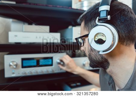 Man turning up the volume on home Hi-Fi stereo for louder music