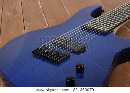 Musical Instrument - Fragment 8-string Blue Electric Guitar Solid-body On A Wood Background