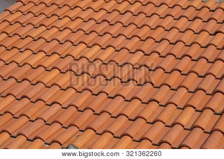 Roof top view. Red tile. The pattern of roof tile. Orange tile roof, abstract background. Roofing texture. Red corrugated tile element of roof. Seamless pattern.