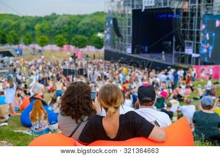 Friends watching concert at open air music festival, back view, stage and spectators at background