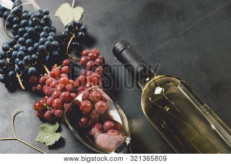 White Wine Bottle, Wineglasses, Fresh Grapes And Leaves On Black Wood Background. Flat Lay, Top View