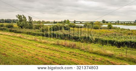 Panorama Photo Of A Dutch Landscape. Behind The Fence At The Foot Of The Dike Is The Tiendgorzen Nat