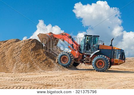 Backhoe Loader Or Bulldozer - Excavator With Clipping Path On A Background With Blue Sky And Clouds.