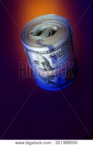 financial image of close up rolled and rubber banded American one hundred dollar bills pile on desk