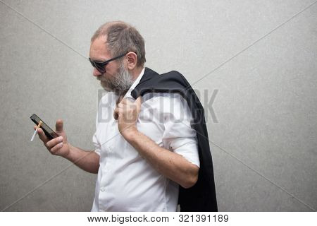 Man In Glasses With A Beard And Jacket Holds A Phone And A Cigarette