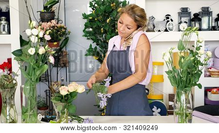 Professional Woman Florist Talks On Smartphone Taking Order And Makes Bouquet Working In Flower Shop
