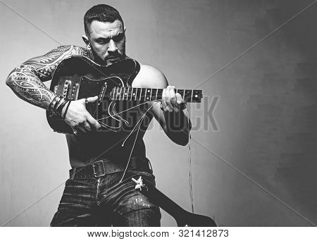Guitar as weapon. Brutal latino man playing the broken guitar. Hispanic guitarist performing music on electric guitar. Bearded guitarist with string guitar in strong hands, copy space. poster